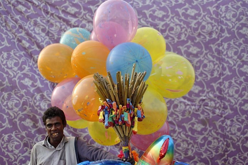 A vendor selling balloons waits for customers on the banks of the river Yamuna during the Hindu religious festival of Chatt Puja in New Delhi on Oct 29, 2014.Two foreign tourists on holiday in India unwittingly landed in jail this week after st