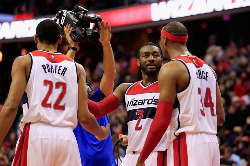 Otto Porter Jr. #22, John Wall #2, and Paul Pierce #34 of the Washington Wizards celebrate following their 96-94 overtime win at Verizon Center on Nov 5, 2014 in Washington, DC. The red-hot Washington Wizards kept their win streak alive with a 9