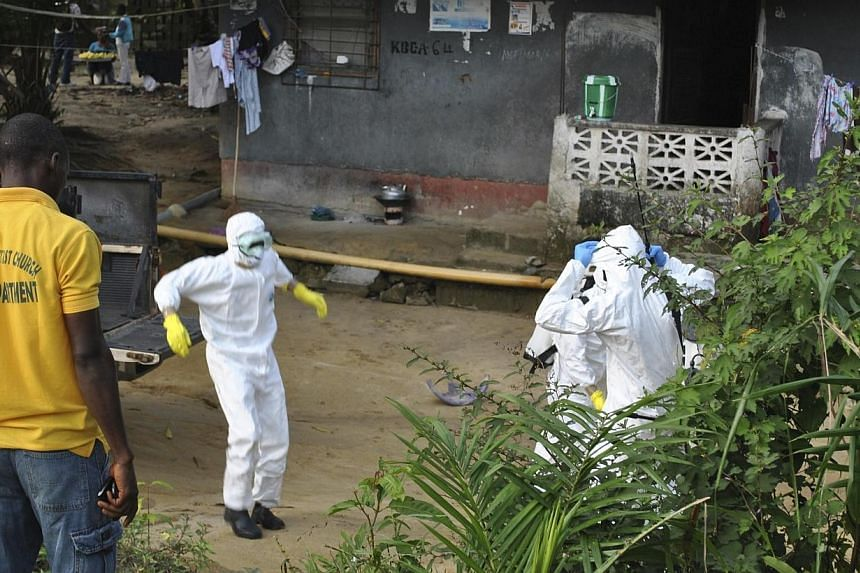 Medical staff wearing protective suits gather at a health facility near the Liberia-Sierra Leone border in western Liberia on Nov 5, 2014.The number of Ebola cases is surging in Sierra Leone as the country suffers from a lack of treatment centr