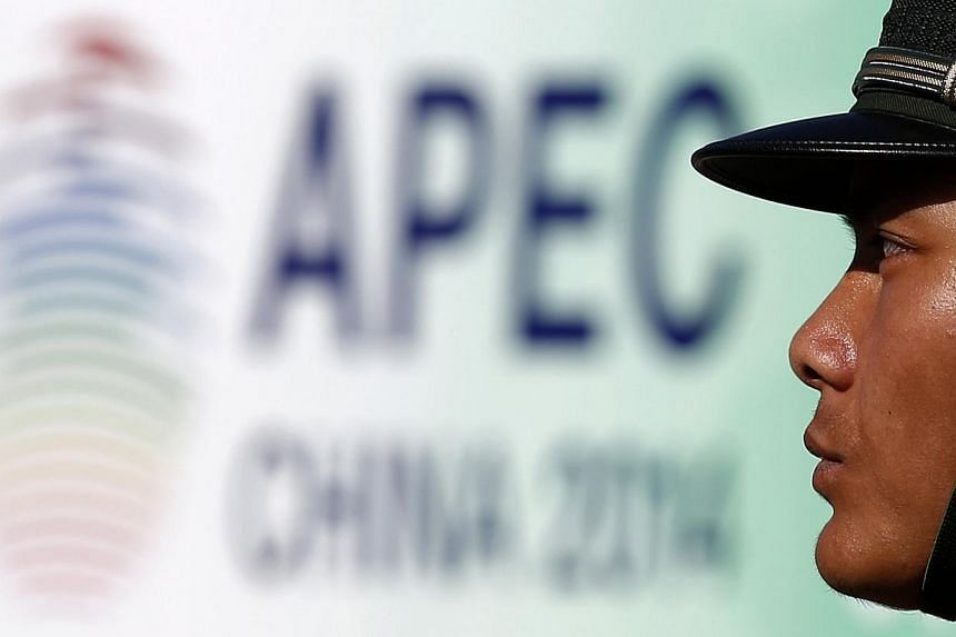 A paramilitary policeman stands guard next to a banner for the Apec Concluding Senior Officials' Meeting in Beijing, Nov 5, 2014.From territorial disputes with neighbours to rivalry with the United States, China is setting aside some of its big