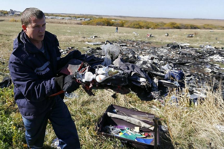 An Emergencies Ministry member walks near belongings and wreckage at the site where downed Malaysia Airlines Flight MH17 crashed, in the Donetsk region of Ukraine on Oct 13, 2014.Dutch investigators expect to begin recovering wreckage from the
