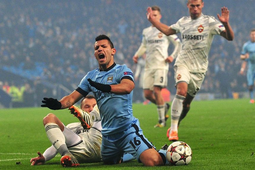 Manchester City's Argentinian striker Sergio Aguero (C) is challenged by CSKA Moscow's defender Sergey Ignashevich before he was shown the yellow card for diving during the matchagainst CSKA Moscow. -- PHOTO: AFP