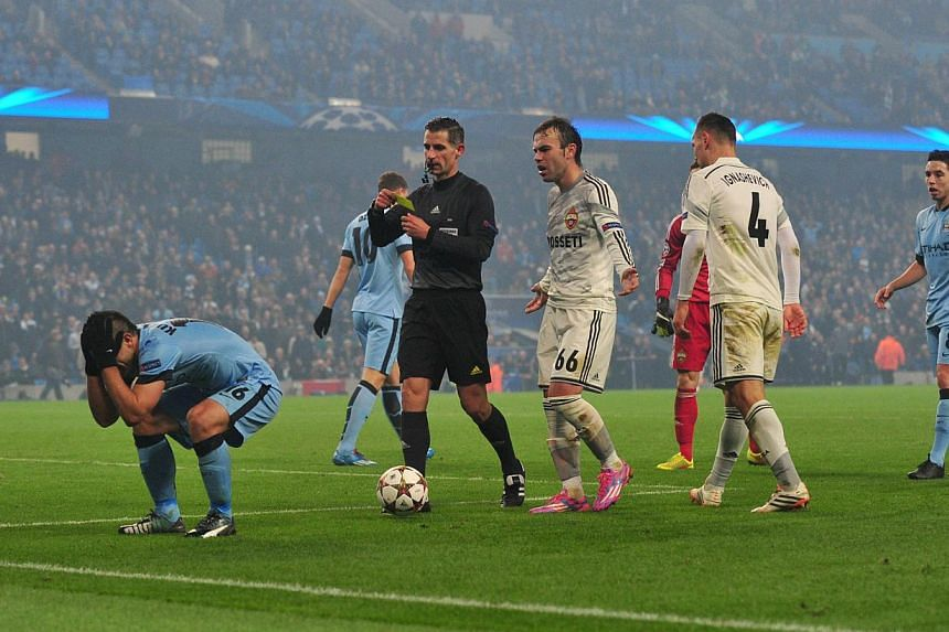 Manchester City's Argentinian striker Sergio Aguero (L) gets a yellow card for diving during the UEFA Champions League Group E football match between Manchester City and CSKA Moscow at the Etihad Stadium in Manchester on Nov 5. -- PHOTO: AFP