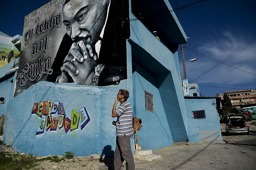 A tourist stands in front of a Martin Luther King graffiti in the Cova da Moura neighborhood of Amadora on the outskirts of Lisbon. One of the most ill reputed suburban neighborhoods of Europe, it is often likened to the favelas of Brazil and the tow