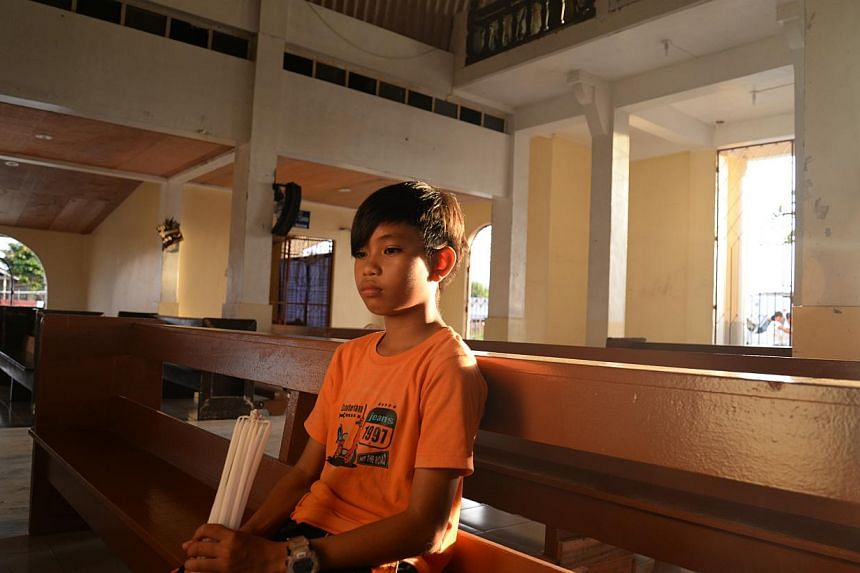 John Paul Lacandazo, 10, sits inside a church in San Joaquin village in Palo town, Leyte province. The boy lost his parents and two brothers when Typhoon Haiyan struck on Nov 8, 2013. -- ST PHOTO: RAUL CAPUNPON DANCEL