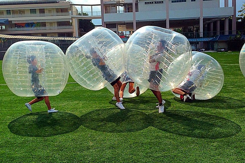 Participants cocooned within giant bubbles bump, shove and crash into one another during a game. -- PHOTO: ZOVB SINGAPORE