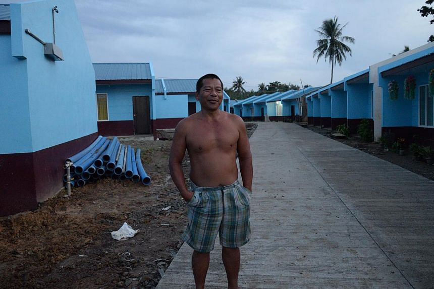 Mr Justino Goco, 51, a bus driver, stands outside his new home at a permanent relocation site in Tacloban city. -- ST PHOTO: RAUL CAPUNPON DANCEL