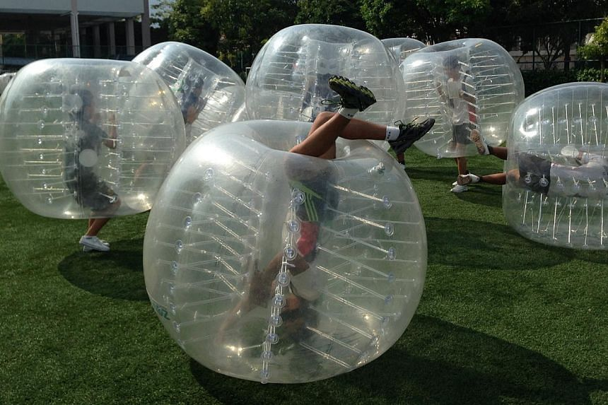 Participants cocooned within giant bubbles bump, shove and crash into one another during a game. -- PHOTO:ZOVB SINGAPORE
