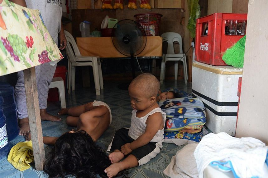 John Paul Aler, an eight-year-old suffering from growth hormone deficiency, watches one of his sisters sleeping inside their bunkhouse at a temporary settlement in Caibaan village in Tacloban city. -- ST PHOTO: RAUL CAPUNPON DANCEL