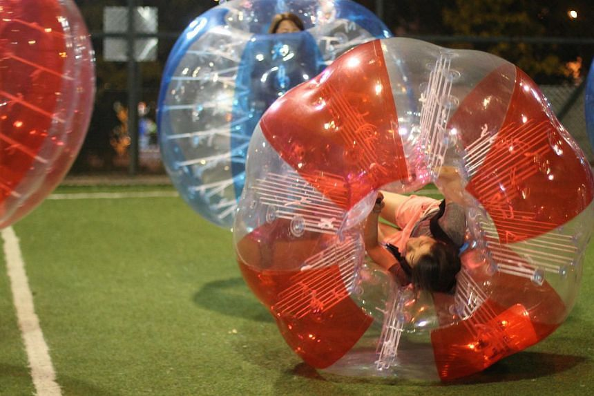 Participants cocooned within giant bubbles bump, shove and crash into one another during a game. -- PHOTO:BUBBLE BUMP SINGAPORE