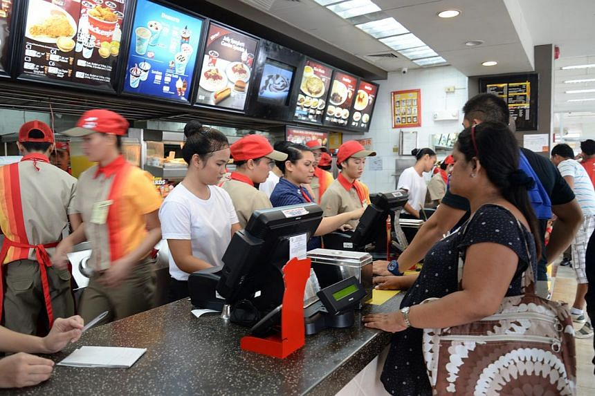 People ordering at an outlet of popular fast-food chain Jollibee in Tacloban city. -- ST PHOTO: RAUL CAPUNPON DANCEL