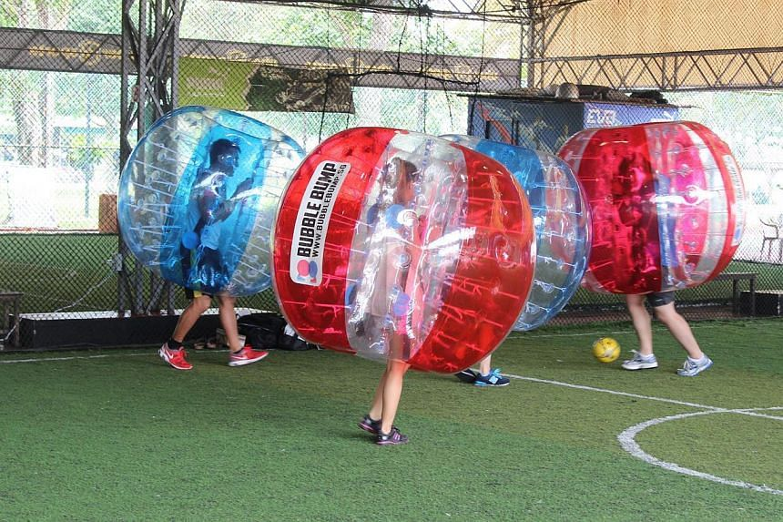 Participants cocooned within giant bubbles bump, shove and crash into one another during a game. -- PHOTO: BUBBLE BUMP SINGAPORE