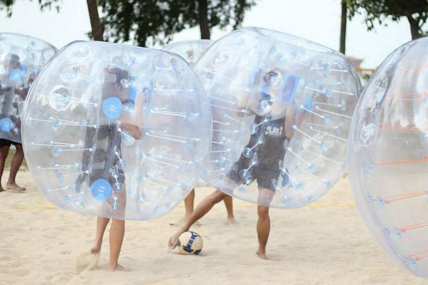 Participants cocooned within giant bubbles bump, shove and crash into one another during a game. -- PHOTO:VAKK SINGAPORE