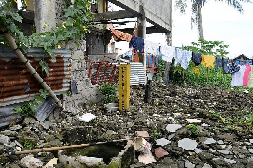 """A low cement beam marks the edge of the 40m""""no-build zone"""" that the government has declared along coasts that wrap Tacloban city, a provincial capital in central Philippines. -- ST PHOTO: RAUL CAPUNPON DANCEL"""