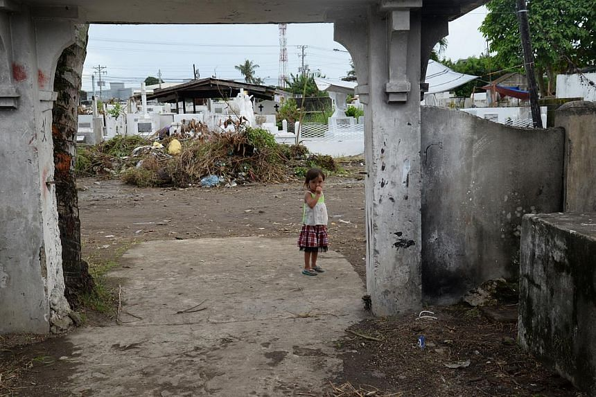 A young girl stands at the threshold of one of the gateways of a public cemetery in Tacloban city on the even of All Soul's Day, a religious holiday in the Philippines for remembering the dead every Oct 31. -- ST PHOTO: RAUL CAPUNPON DANCEL