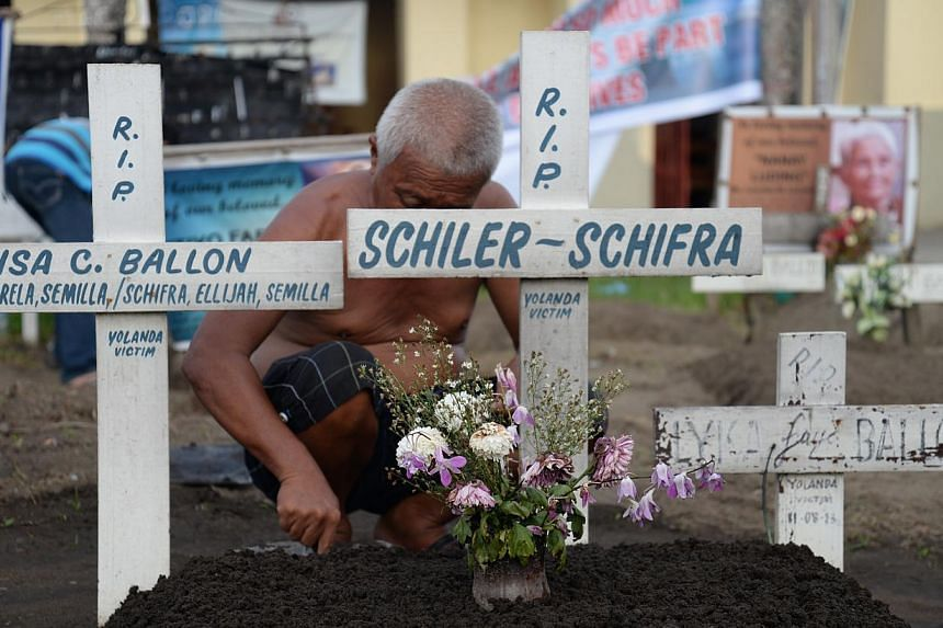 An elderly man cleans the grave of close relatives he lost when Typhoon Haiyan struck central Philippines on Nov 8, 2013. -- ST PHOTO: RAUL CAPUNPON DANCEL