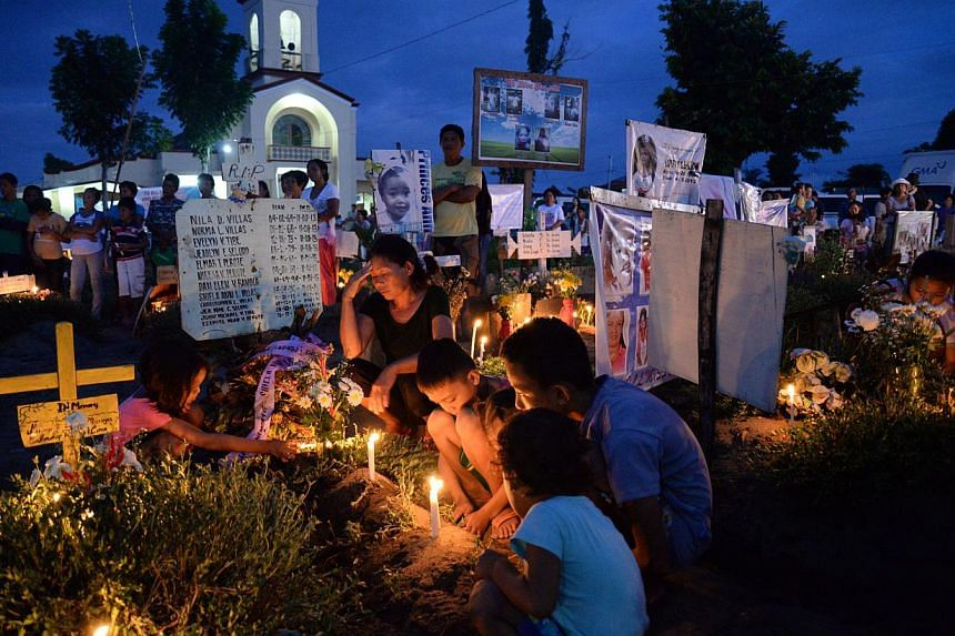 A family grieves for about a dozen kin on All Soul's Day, a religious holiday in the Philippines for remembering the dead every Oct 31, inside a makeshift cemetery at the front lawn of a church in San Joaquin village in Palo town, Leyte province. &nb