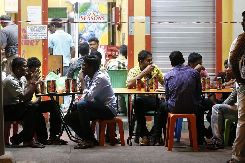 People drinking beer at a shop in Little India. The majority of people polled by the Ministry of Home Affairs (MHA) are strongly supporting proposals to restrict the consumption of alcohol in public. -- PHOTO: ST FILE