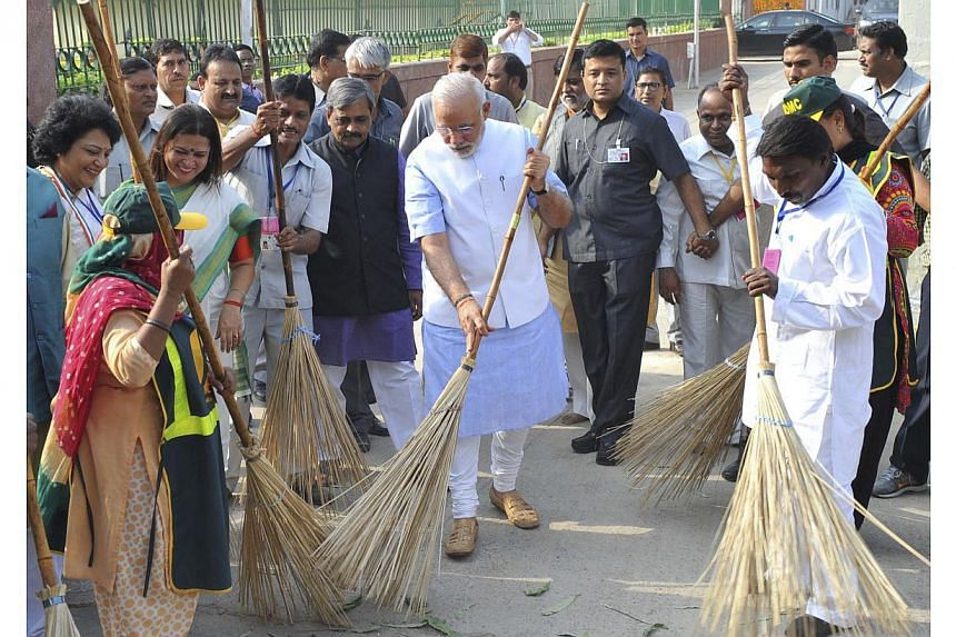 India's Prime Minister Narendra Modi (centre) cleans a road as he launches the Swachh Bharat Abhiyan, or Clean India Mission, in New Delhi in this Oct 2, 2014, picture provided by India's Press Information Bureau. -- PHOTO: REUTERS