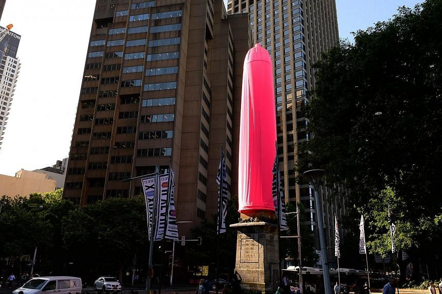 A gaint gaint condom is seen over a heritage-listed obelisk at Hyde Park in Sydney on Nov 7, 2014.An 18-metre bright pink condom raised eyebrows in Sydney on Friday after it was erected over a Sydney landmark as part of a new awareness campaign