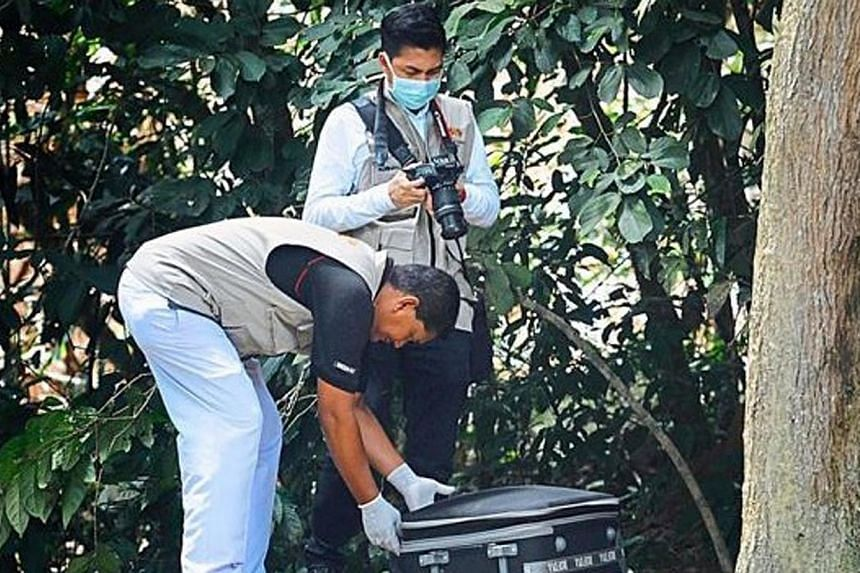 Penang Hospital forensic personnel closing the luggage bag with the body part inside to bring it to the hospital for a post-morterm.A pair of mutilated legs believed to be that of a murdered foreigner was found on Friday at the Pulau Burung dum