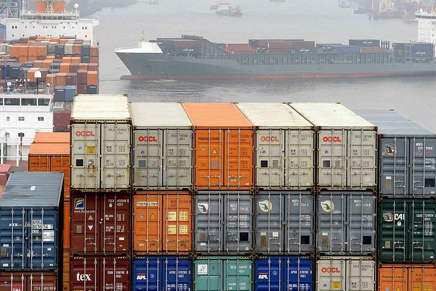 Containers are loaded at the container terminal Altenwerder in the harbour in Hamburg on Nov 18, 2013. -- PHOTO: REUTERS