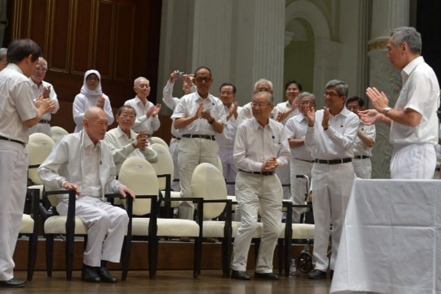 People's Action Party (PAP) members applaud for former prime minister Lee Kuan Yew (second from left, seated) at the PAP's 60th anniversary celebration at Victoria Concert Hall . -- ST PHOTO: CAROLINE CHIA