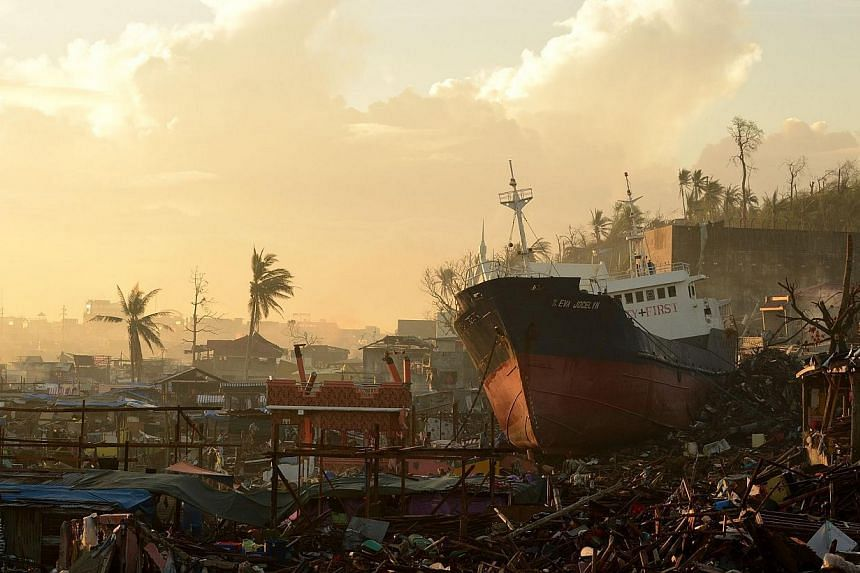 A ship is washed ashore crushing houses in Tacloban, Leyte Province, after Super Typhoon Haiyan swept over the central Philippines on Nov 25, 2013.Philippine President Benigno Aquino on Friday defended the pace of rebuilding in communities rava
