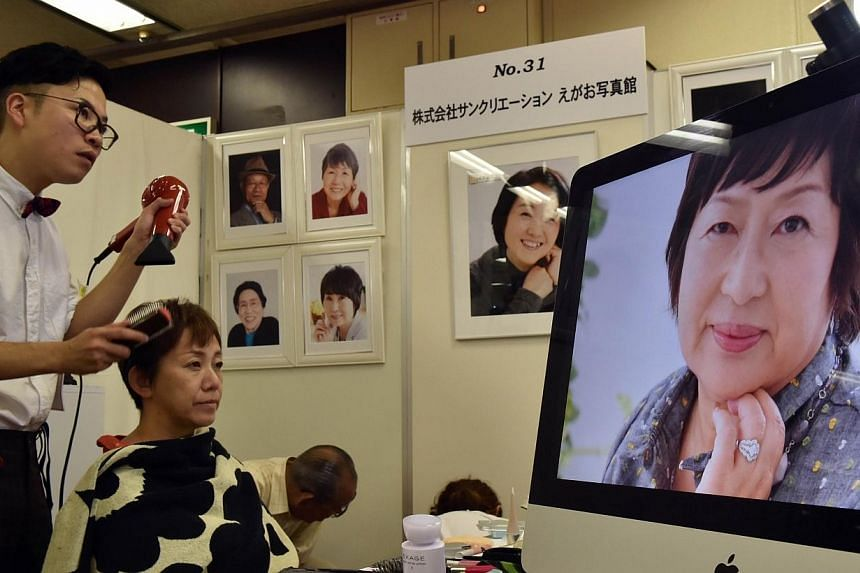 "A woman (centre) has her hair styled before sitting for a photograph that will be used for her deceased portrait, at the annual ""Shukatsu Festa 2014"" funeral business fair in Tokyo on Aug 24, 2014. -- PHOTO: AFP"