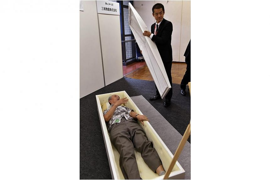 "A man lies in a coffin, while a coffin maker employee closes the cover at the annual ""Shukatsu Festa 2014"" funeral business fair in Tokyo on Aug 24, 2014. -- PHOTO: AFP"