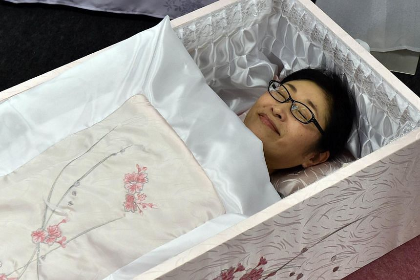 "A woman lies in a coffin at the annual ""Shukatsu Festa 2014"" funeral business fair in Tokyo on August 24, 2014."
