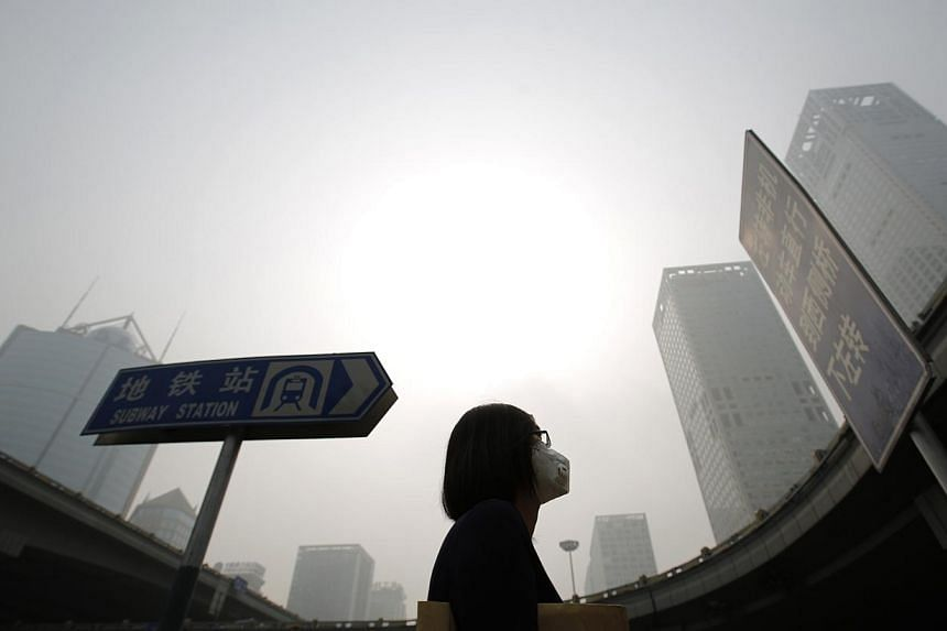 A woman wearing a mask makes her way on a street amid heavy haze and smog in Beijing, in this October 11, 2014 file picture. China's capital is expected to face more heavy smog from October 29, 2014 as it battles to try to guarantee air quality ahead