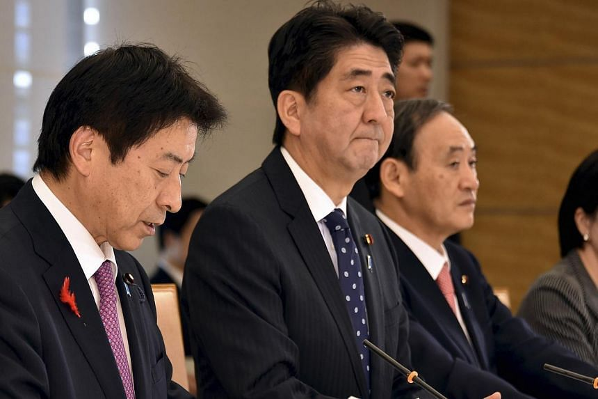 Japan's Prime Minister Shinzo Abe (second from left), flanked by Labour, Health and Welfare Minister Yasuhisa Shiozaki (left), Chief Cabinet Secretary Yoshihide Suga (second from right) and Internal Affairs and Communications Minister Sanae Takaichi