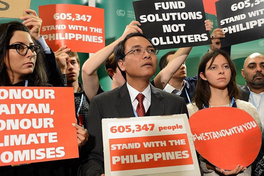 A Nov 19, 2013 picture shows the Philippines' head negotiator Naderev Sano (centre) and supporters holding banners at the United Nations Climate Change Conference COP 19 in Warsaw, Poland. Sano will on Saturday reach ground zero of the strongest typh