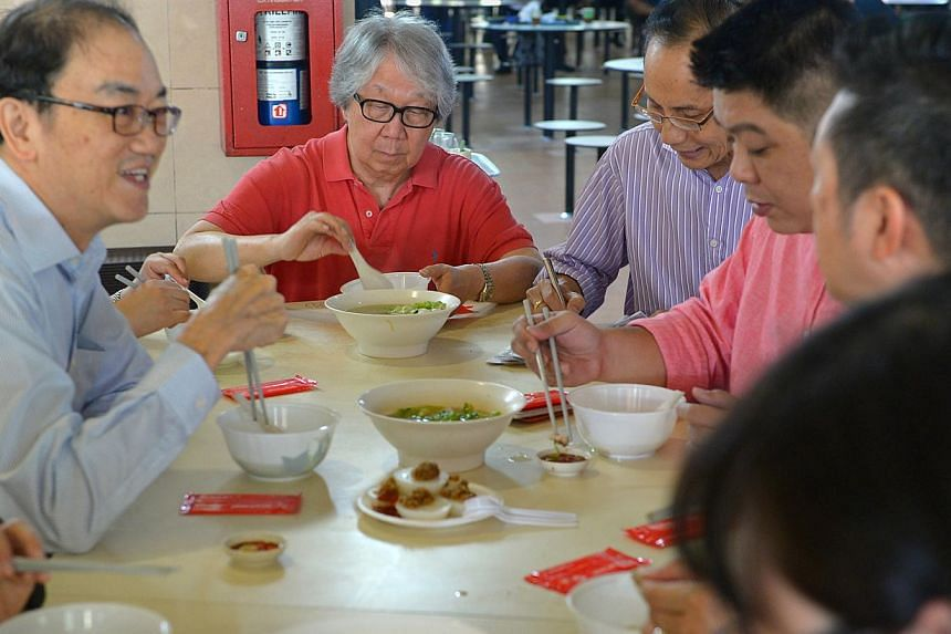 Professor Tommy Koh (centre, in red shirt) tries out the fish soup at from Ng Seng Heng at Pek Gio Market with the rest of the judges, as part of the annual Singapore Hawker Masters awards, which began on Friday, Nov 7. -- ST PHOTO: NG SOR LUAN