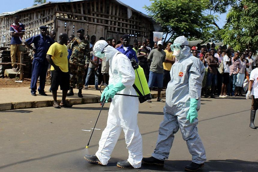 Health workers spray themselves with chlorine disinfectants after removing the body a woman who died of Ebola virus in the Aberdeen district of Freetown, Sierra Leone, Oct 14, 2014. The raging Ebola outbreak has likely killed far more people than the