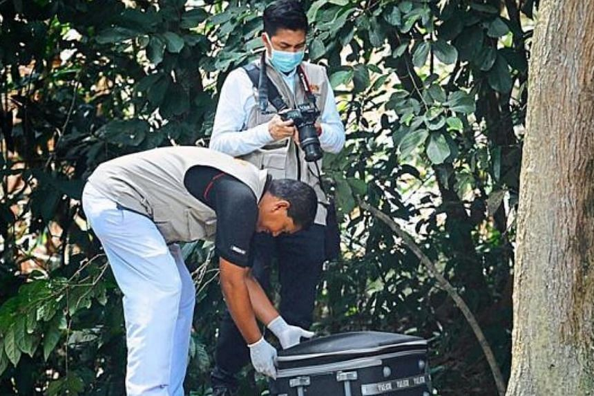 Penang Hospital forensic personnel close a luggage bag with body parts inside to bring it to the hospital for a post-mortem. -- PHOTO: THE STAR/ASIA NEWS NETWORK