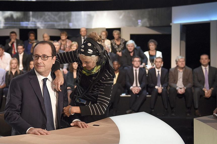 French President Francois Hollande arrives on stage before appearing on a TF1 television prime time news live broadcast at their studios in Aubervilliers, near Paris, Nov 6, 2014. Hollande, the most unpopular French president in history, admitted on