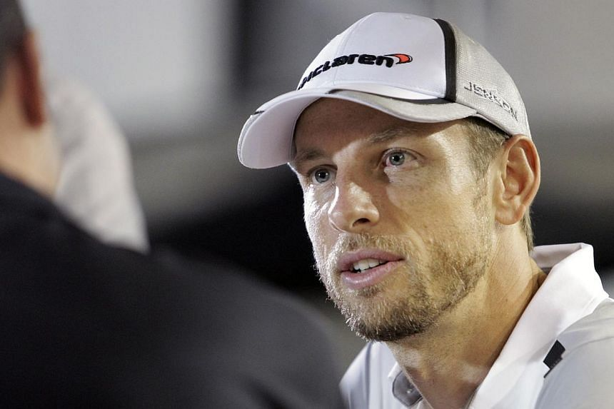 McLaren Formula One driver Jenson Button of Britain is interviewed outside his team hospitality suite at the paddock area of Singapore F1 Grand Prix in Singapore Sept 18, 2014.Button dropped a heavy hint on Thursday that he is prepared to walk