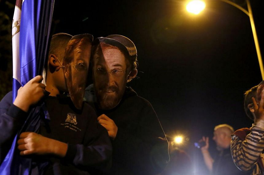 Jewish extremists gather on Nov 6, 2014 near the Old City of Jerusalem, at the site where a Palestinian man recently tried to assassinate Rabbi Yehuda Glick (masks), a hardline campaigner for Jewish prayer rights at the Al-Aqsa mosque compound, befor