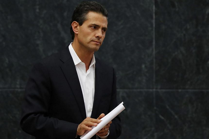 Mexico's President Enrique Pena Nieto looks on after addressing the media about a private meeting with the relatives of 43 missing students on Oct 29, 2014.Pena Nieto has shortened an upcoming trip to major summits in China and Australia amid a
