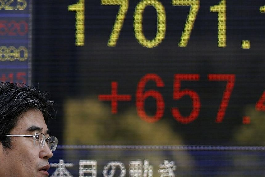 A pedestrian walks past an electronic board showing the Japan's Nikkei average outside a brokerage in Tokyo on Nov 4, 2014.Tokyo stocks opened 0.84 per cent higher on Friday following rallies on Wall Street and a rebound in the US dollar against the