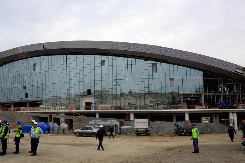 """A picture taken on Oct 17, 2014, shows employees standing in front of the swimming pool of the Aquatics Center in Baku.The head of next year's inaugural European Games in Azerbaijan said he had """"no concerns"""" on Saturday about Baku not being rea"""