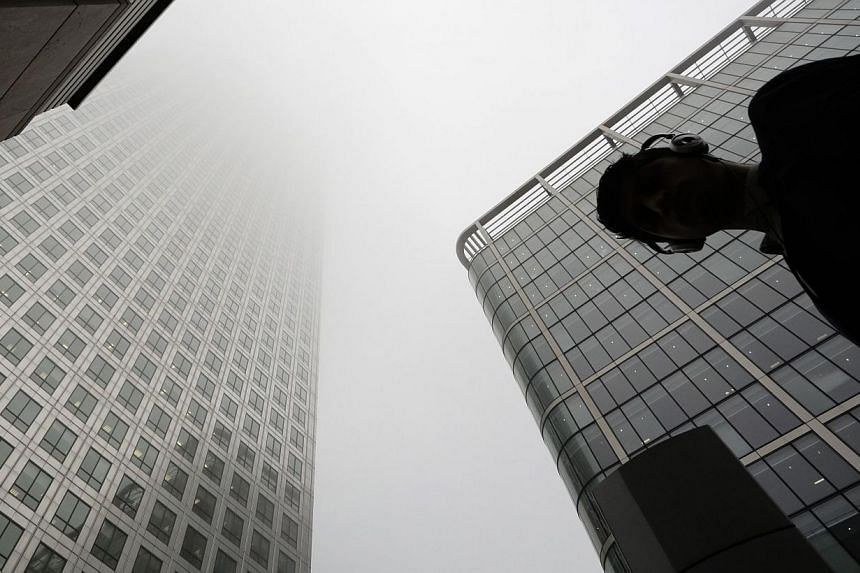 A man walks past a building in the morning mist at London's financial district of Canary Wharf on Sept 16, 2014.Britain's competition watchdog launched a full investigation into banking services for small business customers and personal account