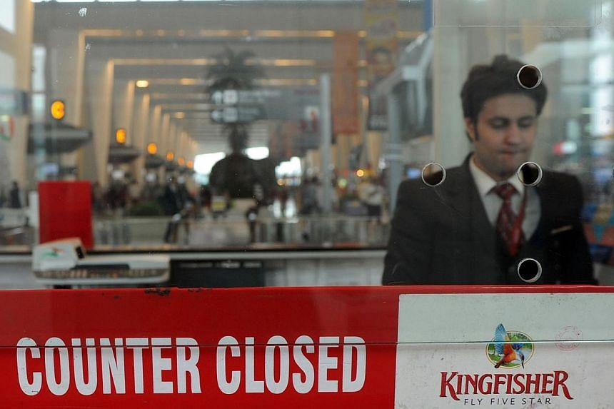 An Indian customer service representative stands inside the closed booth of a Kingfisher Airlines booking counter at Indira Gandhi International Airport in New Delhi on Oct 20, 2012.Shares of India's grounded Kingfisher Airlines face suspension
