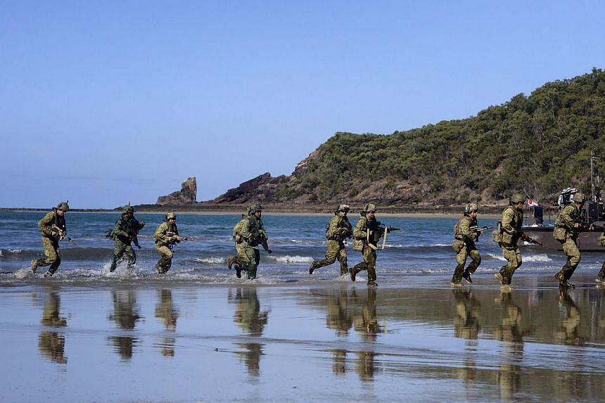 Troops from the Singapore Guards Formation of the Singapore Armed Forces and troops from the Seventh Australian Regiment of the Australian Defence Force land on the beach during a preview of Exercise Trident which is part of Exercise Wallaby at Fresh