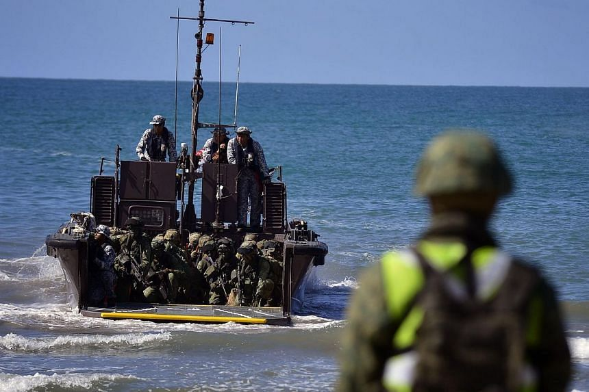 Troops from the Singapore Guards Formation of the Singapore Armed Forces and troops from the Seventh Australian Regiment of the Australian Defence Force prepare to land on the beach from a Fast Craft Utility during the Ship-to-Shore projection during