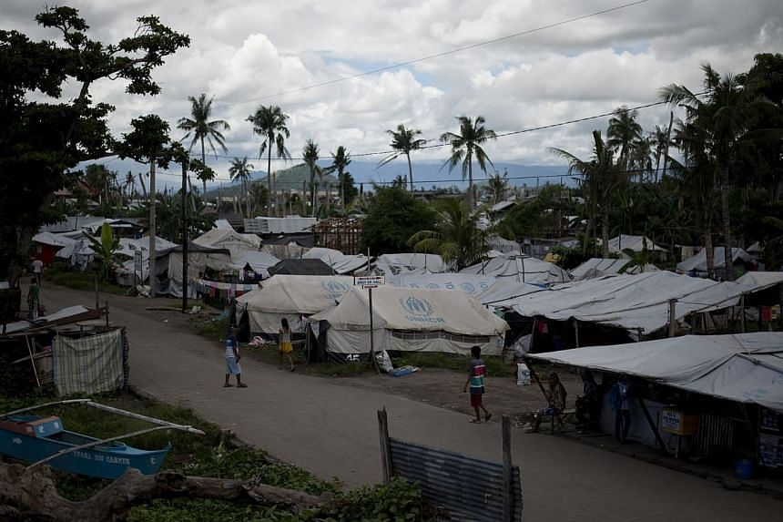 FAR LEFT:Families are still staying in a tent city that was set up for survivors of the typhoon in Tacloban, which was largely destroyed in November last year. Some 6,300 people died across central Philippines as Super Typhoon Haiyan whipped up the s