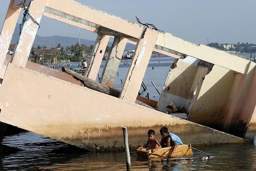 Boys paddling on a makeshift boat made of a styrofoam box next to a house swept away by Typhoon Haiyan in Tacloban city. A year on, only 50 families out of over 14,500 families in evacuation centres have permanent housing. Tacloban city residents pas