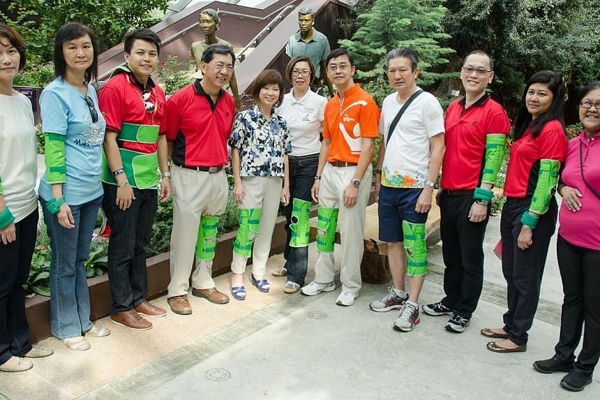 Guest of honour, Dr Amy Khor (centre), wearing a knee restrictor, takes a photo with Building and Construction Authority CEO John Keung (fourth from left), Gardens by the Bay deputy CEO Peggy Chong (sixth from right), National Council of Social Servi